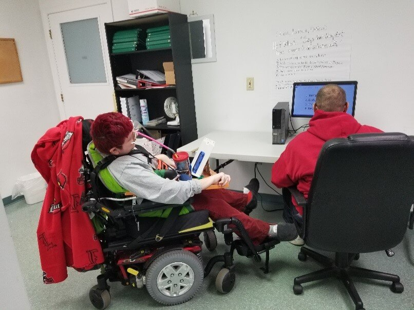 Image of disabled person and helper working on a computer